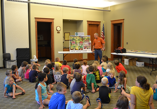 Al Schilling, Member Advocate, uses the Hazard Hamlet display to teach children how to be safe around electricity.